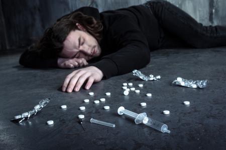 Foto von verzweifelten jungen Drogensüchtigen allein im Dunkeln nach der Einnahme von Heroin und Pillen liegen