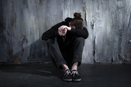 addiction: Photo of desperate young drug addict wearing hood and sitting alone in dark