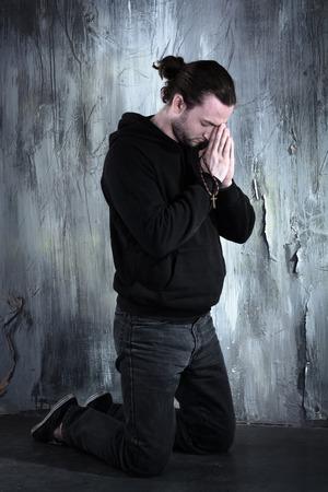 orando: Foto del drogadicto desesperado joven orando y sentado solo en la oscuridad