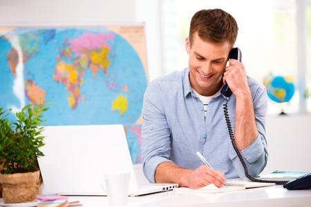 Foto von männlichen Reisebüro. Junge männliche Betreiber lächelnd, Gespräch am Telefon und bietet Urlaubsmöglichkeiten für die Kunden. Reisebüro Büro-Interieur mit großen Weltkarte