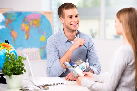 Bild av manlig resebyrå och ung kvinna. Ung man leende och erbjuder semesteralternativ för kvinnlig turist. Resebyrå kontor interiör med stor världskarta