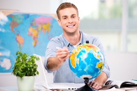 Photo of male travel agent. Young man smiling, looking at camera, choosing place to travel and pointing at globe. Travel agency office interior with big world map