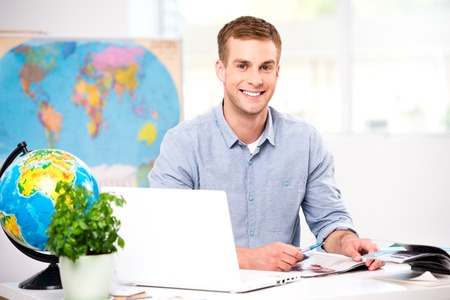 Photo of male travel agent. Young man smiling and looking at camera. Travel agency office interior with big world map