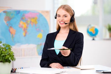 Foto van vrouwelijke reisbureau. Jonge vrouw met een koptelefoon glimlachen, het voorstellen toeristische boekje en kijken naar de camera. Reisbureau kantoor interieur met grote kaart van de wereld Stockfoto