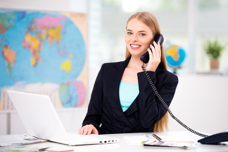 Foto van vrouwelijke reisbureau. Jonge vrouw praten over de telefoon, lacht en kijkt naar de camera. Reisbureau kantoor interieur met grote kaart van de wereld