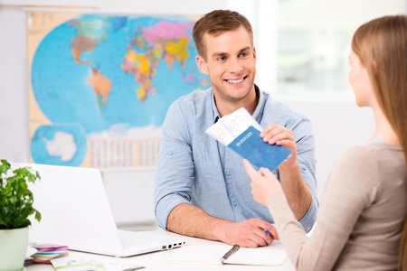 travel agency: Photo of male travel agent and young woman. Young man smiling and giving tickets passport with visa to female tourist. Travel agency office interior with big world map