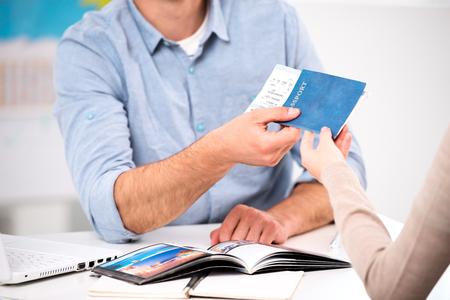 viagem: Feche acima da foto do agente de viagens do sexo masculino e jovem. Homem novo que dá bilhetes e passaporte com visto de turista para o feminino