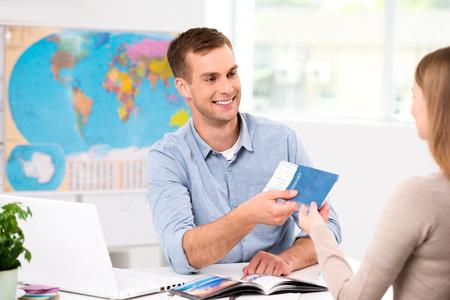 person traveling: Foto de agente de viajes varón y mujer joven. Hombre joven sonriendo y dando billetes, pasaporte con visa de turista. Viaje interior oficina de la agencia con gran mapa del mundo