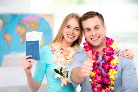 honeymoon couple: Photo of young tourists with hawaiian necklaces. Young man and woman smiling and holding tickets and passport with visa. Man showing thumb up. Travel agency office interior with big world map