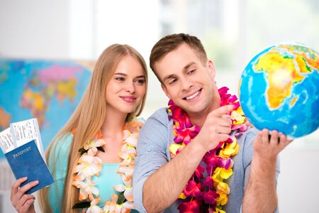 Photo of young tourists with hawaiian necklaces. Young man and woman smiling, holding tickets and passport. Couple choosing country on globe. Travel agency office interior with big world map Stock Photo