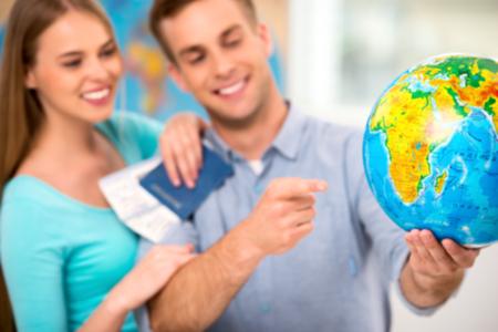 チケットとパスポートの若い観光客の写真。世界中の国の選択のカップル。地球に焦点を当てる