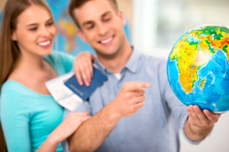Photo of young tourists with tickets and passport. Couple choosing country on globe. Focus on globe Stock Photo
