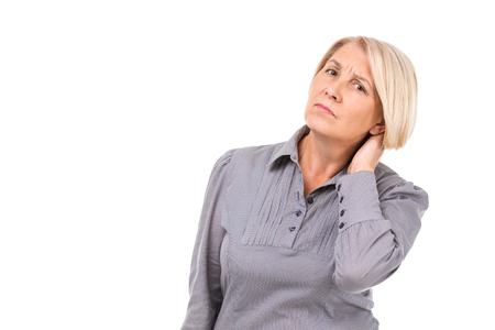 only women: Portrait of senior blonde woman standing isolated on white background. Woman wearing grey blouse. Woman looking at camera sadly. Woman suffering from neck pain Stock Photo
