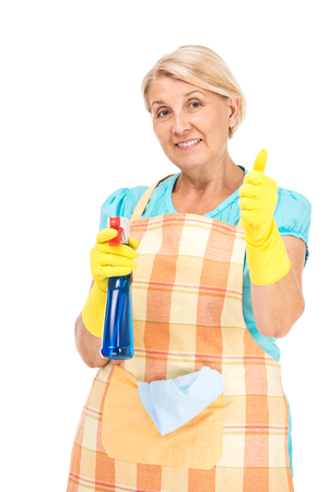 rubber: Portrait of senior blonde woman standing isolated on white background. Woman wearing apron and yellow rubber gloves. Smiling woman looking at camera, showing thumb up and holding liquid for cleaning