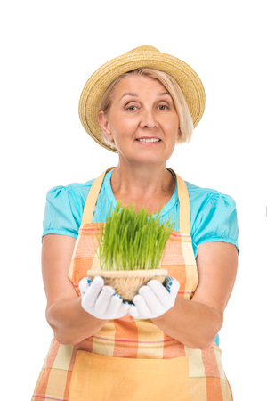 gardening: Portrait of senior blonde woman standing isolated on white background. Woman wearing apron, straw hat and gloves. Smiling woman looking at camera and holding green grass Stock Photo