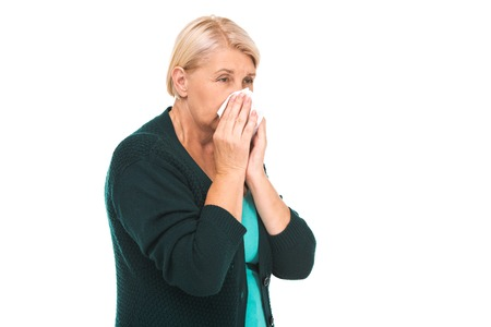 running nose: Portrait of senior blonde woman standing isolated on white background. Unhappy sick woman suffering from running nose Stock Photo