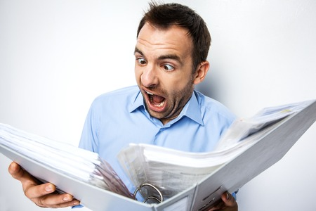 eyes wide: Funny photo of businessman with beard wearing shirt. Shocked businessman looking at folder full of documents with eyes wide open. Isolated on white background
