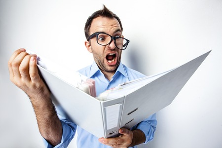 humor: Funny photo of businessman with beard wearing shirt and glasses. Shocked businessman looking at folder full of documents with eyes wide open. Isolated on white background Stock Photo