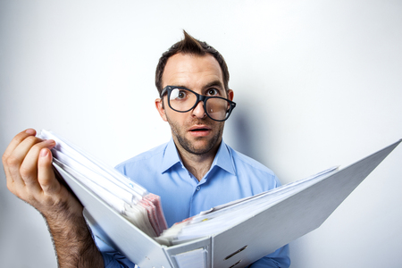 eyes wide: Funny photo of businessman with beard wearing shirt and glasses. Surprised businessman looking at camera with eyes wide open and holding folder full of documents. Isolated on white background Stock Photo