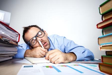 nariz: Foto divertida del hombre de negocios con barba vestido con camisa y gafas. Hombre de negocios con exceso de trabajo que duerme en la mesa llena de documentos con la pluma en la nariz. Aislado en el fondo blanco