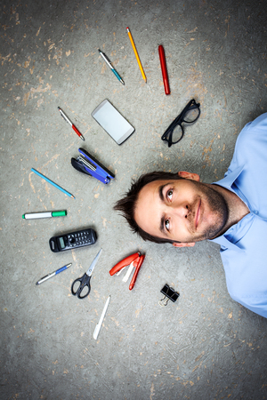 funny glasses: Top view funny photo of businessman with beard wearing shirt. Businessman thoughtfully looking up and lying on floor full of office supplies Stock Photo