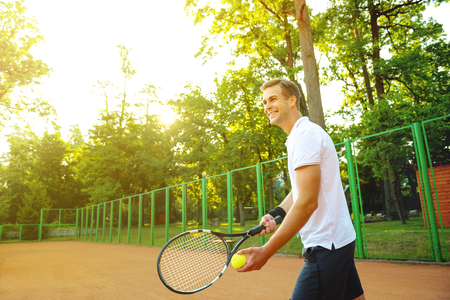 healthy men: Picture of handsome young man on tennis court. Man playing tennis. Man is ready to throw tennis ball. Beautiful forest area as background Stock Photo