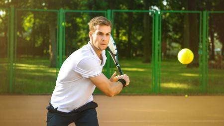 テニスコートでハンサムな若い男の写真。テニス男。男打撃テニス ボール。背景として美しい森林面積 写真素材