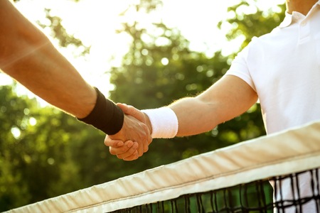 tennis court: Close up photo of young men on tennis court. Men playing tennis. Men shaking hands above net before game. Beautiful forest area as background
