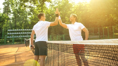 Picture of handsomev young men on tennis court. Man playing tennis. Man giving each other high five. Beautiful forest area as background