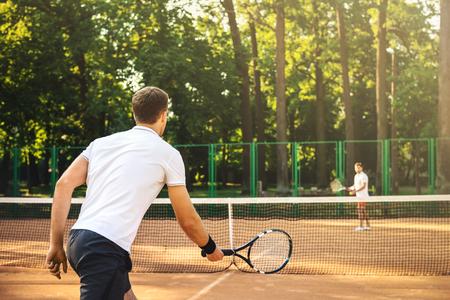 Bild von hübschen jungen Männer auf Tennisplatz. Männer Tennis spielen. Man ist bereit, Tennisball zu treffen. Schöne Waldfläche als Hintergrund Lizenzfreie Bilder