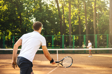 Picture of handsome young men on tennis court. Men playing tennis. Man is ready to hit tennis ball. Beautiful forest area as background