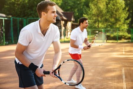 jugando tenis: Cuadro de apuestos jóvenes en pista de tenis. Hombres jugando al tenis. El hombre está listo para golpear una pelota de tenis. Área de bosque hermoso como fondo