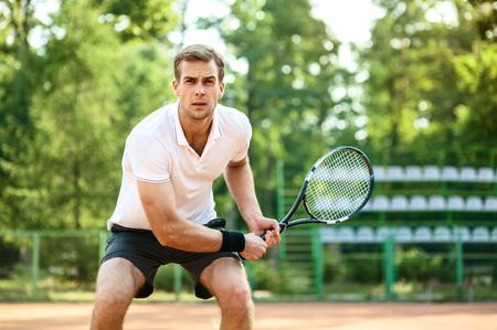 テニスコートでハンサムな若い男の写真。テニス男。男はテニスボールをヒットする準備ができています。背景として美しい森林面積