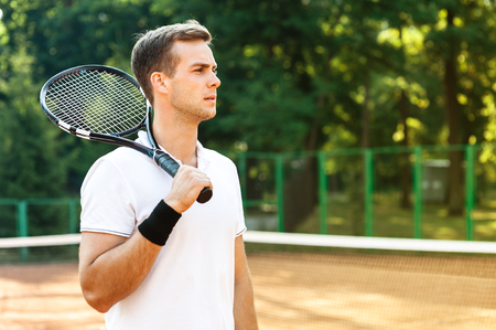 hombre deportista: Imagen del hombre joven y guapo en la cancha de tenis. Hombre que juega a tenis. Hombre que sostiene la raqueta de tenis en el hombro. �rea de bosque hermoso como fondo