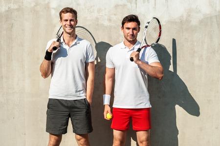tenis: Cuadro de apuestos jóvenes en pista de tenis. Hombres sonriendo con alegría, mirando a la cámara y la celebración de raquetas de tenis