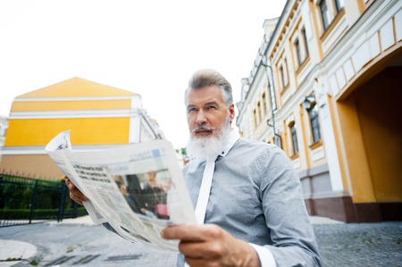cool guy: Portrait of stylish handsome adult man with beard standing outdoors. Man holding newspaper and wearing tie