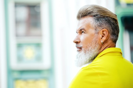 cool man: Portrait of stylish handsome adult man with beard standing outdoors. Man wearing yellow T-shirt and looking aside Stock Photo