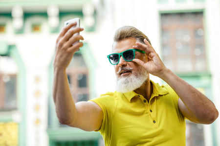 stylish: Portrait of stylish handsome adult man with beard standing outdoors. Man wearing glasses and yellow T-shirt, and making selfie photo with mobile phone