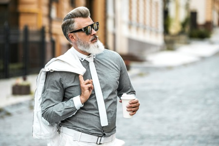 Portrait of stylish handsome adult man with beard standing outdoors. Man wearing tie, holding jacket and cup of coffee