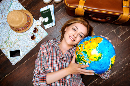 Top view photo of beautiful blonde girl lying on wooden floor. Young woman smiling, holding globe and looking at camera. Passport, tickets, mobile phone, hat, suitcase and map are on floor
