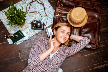 Top view photo of beautiful blonde girl lying on wooden floor. Young woman smiling, holding credit card and looking at camera. Passport, tickets, vintage camera, hat and map are on floor