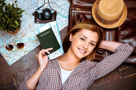 foto carnet: Vista superior de la foto de la hermosa chica rubia acostado en el piso de madera. mujer joven y sonriente, que sostiene el pasaporte y los billetes, y mirando a la c�mara. C�mara de la vendimia, sombrero y un mapa est�n en el piso