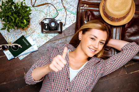 adventure travel: Top view photo of beautiful blonde girl lying on wooden floor. Young woman smiling, showing thumb up and looking at camera. Passport, tickets, vintage camera, hat and map are on floor
