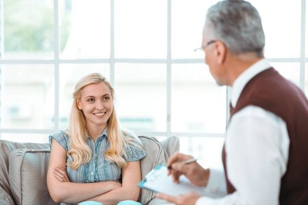 mental illness: Smiling happy young woman talking with psychologist. Psychologist taking notes. There is big window in psychologist office