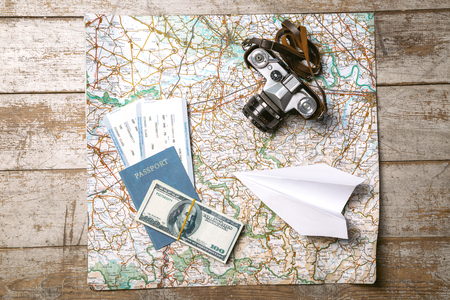 passport: Top view photo of world map, white paper plane, passport, tickets, money and vintage camera. Objects are on light colored wooden floor
