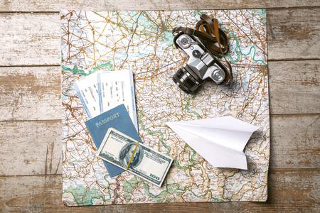 passeport: Vue d'en haut photo de la carte du monde, blanc avion en papier, passeport, billets, de l'argent et un appareil photo vintage. Les objets sont sur le plancher en bois de couleur claire