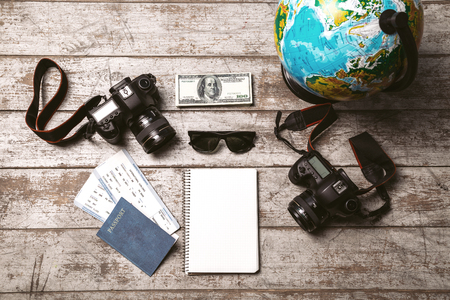 notebook: Top view photo of globe, two professional cameras, notebook, passport, tickets, money and sunglasses. Objects are on light colored wooden floor Stock Photo
