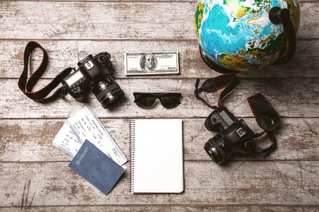 foto carnet: Vista superior foto de globo, dos c�maras profesionales, port�tiles, pasaporte, billetes, dinero y gafas de sol. Los objetos son de la luz piso de madera de color