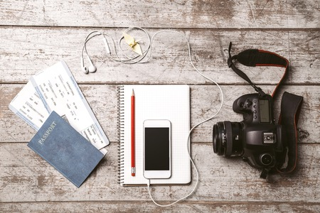 vacation  summer: Top view photo of white mobile phone, professional camera, notebook, passport, tickets, pencil, origami bird and headphones. Objects are on light colored wooden floor Stock Photo