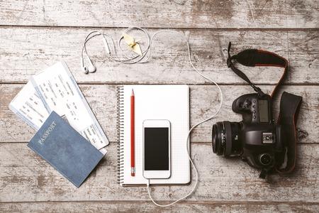 foto carnet: Vista superior foto de tel�fono blanco m�vil, c�mara profesional, cuaderno, pasaporte, billetes, l�piz, p�jaro del origami y los auriculares. Los objetos son de la luz piso de madera de color Foto de archivo